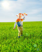 Happy boy playing with toy airplane against blue summer sky and green field background. — Stock Photo
