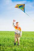 Молодой мальчик, играя с его кайт в зеленое поле. — Стоковое фото
