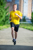 Sporty man jogging in city street park. Outdoor fitness. — Stock fotografie