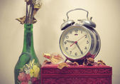 Still life with broken alarm clock, old glass vase with dead ros — Stock Photo