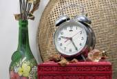 Still life with broken alarm clock, old glass vase with dead ros — Стоковое фото