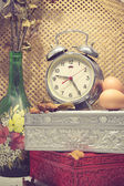 Still life with broken alarm clock, old glass vase with dead ros — Photo