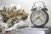 Still life with broken alarm clock, dead flowers, old silver box — Stock Photo