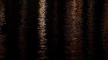 Calm rippling water in the night with artificial tungsten lights, Magic Lantern RAW video — Stock Video