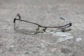 Broken eyeglasses on concrete — Stock Photo