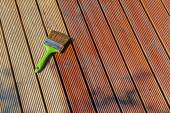 Painting wooden patio deck with protective oil — Stock Photo