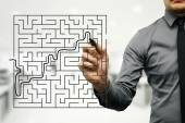 Conceptual image of businessman trying to find way out of maze — Stock Photo