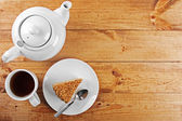Piece of cake and tea pot on wooden table — Stock Photo