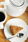 Piece of cake and cup of coffee on wooden table — Stock Photo