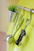 Kitchen utensils hanging on green wall — Stock Photo