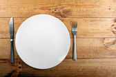 Empty white plate on brown wooden table — Stock Photo