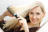 Young smiling woman brushing her long blond hair — Stock Photo