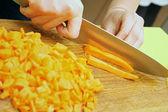 Cutting fresh, raw carrot on the cutting board — Stock Photo