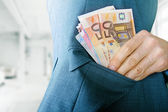 Corruption concept, man putting money in jacket pocket — Stock Photo