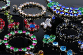 Luxury gemstone jewelry on black glossy table — Stock Photo