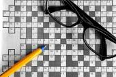 Top view of blank crossword puzzle with black eyeglasses and a p — Stock Photo