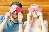 Fall in love concept - young couple holding paper hearts over ey — Stock Photo