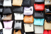 Women handbags hanging on wall in store — Stock Photo
