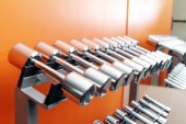 Stand with dumbbells in gym — Stock Photo