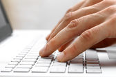 Fingers typing on white laptop computer keyboard — Stock Photo