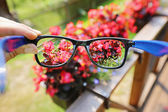 Optical eyeglasses in the hand over blurred flower background — Stock Photo