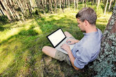 Man is sitting against a tree in the forest, working with his la — Stock Photo
