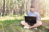 Young man working with his laptop outdoors in nature — Stock Photo
