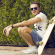 Handsome guy in sunglasses and  board — Stock Photo #74965687