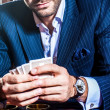 Handsome man in suit plays poker in casino — Stock Photo #74969595