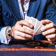 Handsome man in suit plays poker in casino — Stock Photo #74969657