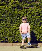 Child in sunglasses with skate in front of green bush — Stock Photo