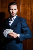 Man in suit holds cards in hand — Stock Photo