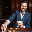 Handsome man in suit plays poker in casino — Stock Photo #74973349