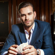Handsome man in suit plays poker in casino — Stock Photo #74973641