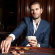 Handsome man in suit plays poker in casino — Stock Photo #74974341