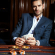 Handsome man in suit plays poker in casino — Stock Photo #74974463