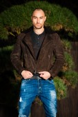 Attractive young man in a brown leather jacket pose in parck — Stock Photo