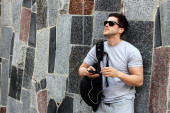 Handsome young guy in sunglasses listens to music from player — Stock Photo