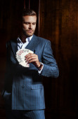 Man in suit holds cards in hand on wooden background — Stock Photo