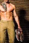 Bonito homem musculoso posando contra fundo elegante goldt — Fotografia Stock