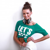 Young beautiful stylish girl in a green jacket poses in front of  camera in  DJ's earphones — Stock Photo