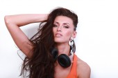 Young beautiful stylish girl in a green jacket poses in front of  camera in  DJ's earphones — Stockfoto