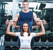 Beautiful woman in gym with personal trainer — Stock Photo