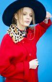 Modelka w czerwony płaszcz i kapelusz niebieski pozuje na zewnątrz — Zdjęcie stockowe