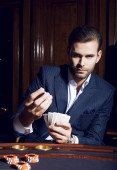 Handsome guy plays cards in casino — Stock Photo