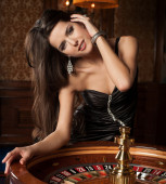 Beautiful brunette plays in casino — Stock Photo