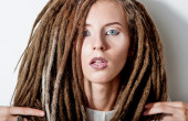 Beautiful girl with dreadlocks poses in white suit — Stock Photo