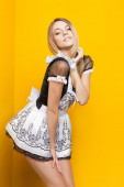 Fashion model in housemaid suit poses on yellow background — Stock Photo