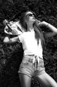 Güneş gözlüğü teşkil longboard yeşil Bush ile şık kız — Stok fotoğraf