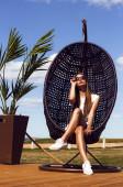 サングラスの美しい長い髪の少女は、ロングボードとポーズします。椅子 — ストック写真